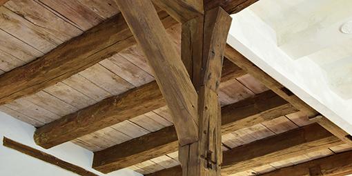 Nahaufnahme einer mit Holzbalken gestützten Decke