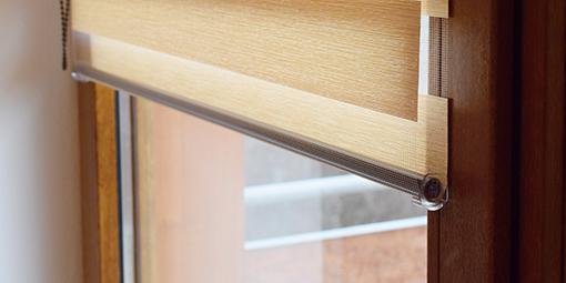 Sonnenschutzrollo vor einem Holzfenster