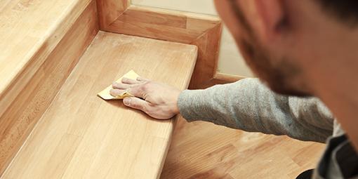 Tischler pflegt fertig gestellte Treppe mit Holzschutz